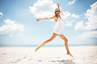 Photo of an active sexy female jumping on beach during summer vacation